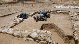 Pekerja muslim dari otoritas barang antik Israel berdoa di reruntuhan salah satu masjid kuno yang baru ditemukan di kota Rahat, gurun Negev pada 18 Juli 2019. Reruntuhan salah satu masjid tertua di dunia tersebut diperkirakan berasal dari Abad ke-7 atau ke-8 Masehi. (MENAHEM KAHANA/AFP)