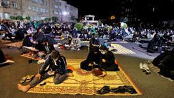 Warga Iran yang sebagian mengenakan masker menghadiri acara kajian dan pengajian Lailatul Qadar, salah satu malam paling suci selama bulan Ramadan, di luar masjid di Teheran, Rabu (13/5/2020). Pemerintah Iran membuka kembali masjid-masjid untuk manyambut malam Lailatul Qadar. (ATTA KENARE/AFP)