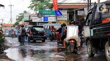 Kendaraan menerobos lubang yang ada di Jalan Raya Bojonggede, Bogor, Jawa Barat, Sabtu (22/2/2020). Jalan Raya Bojonggede yang berlubang hingga kini belum juga diperbaiki pemerintah setempat membuat kondisi lalu lintas tersendat (merdeka.com/Magang/Muhammad Fayyadh)