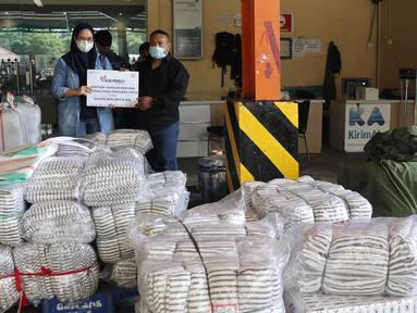Humas PT Askrindo Eka Harumi (kiri) menyerahkan bantuan kepada perwakilan masyarakat NTT di Cargo Bandara Soekarno Hatta, Banten, Kamis (08/04/2021). PT Askrindo berpartisipasi mengirimkan bantuan tanggap bencana ke Nusa Tenggara Timur melalui CSC Garuda Indonesia. (Liputan6.com/Pool/Askrindo)