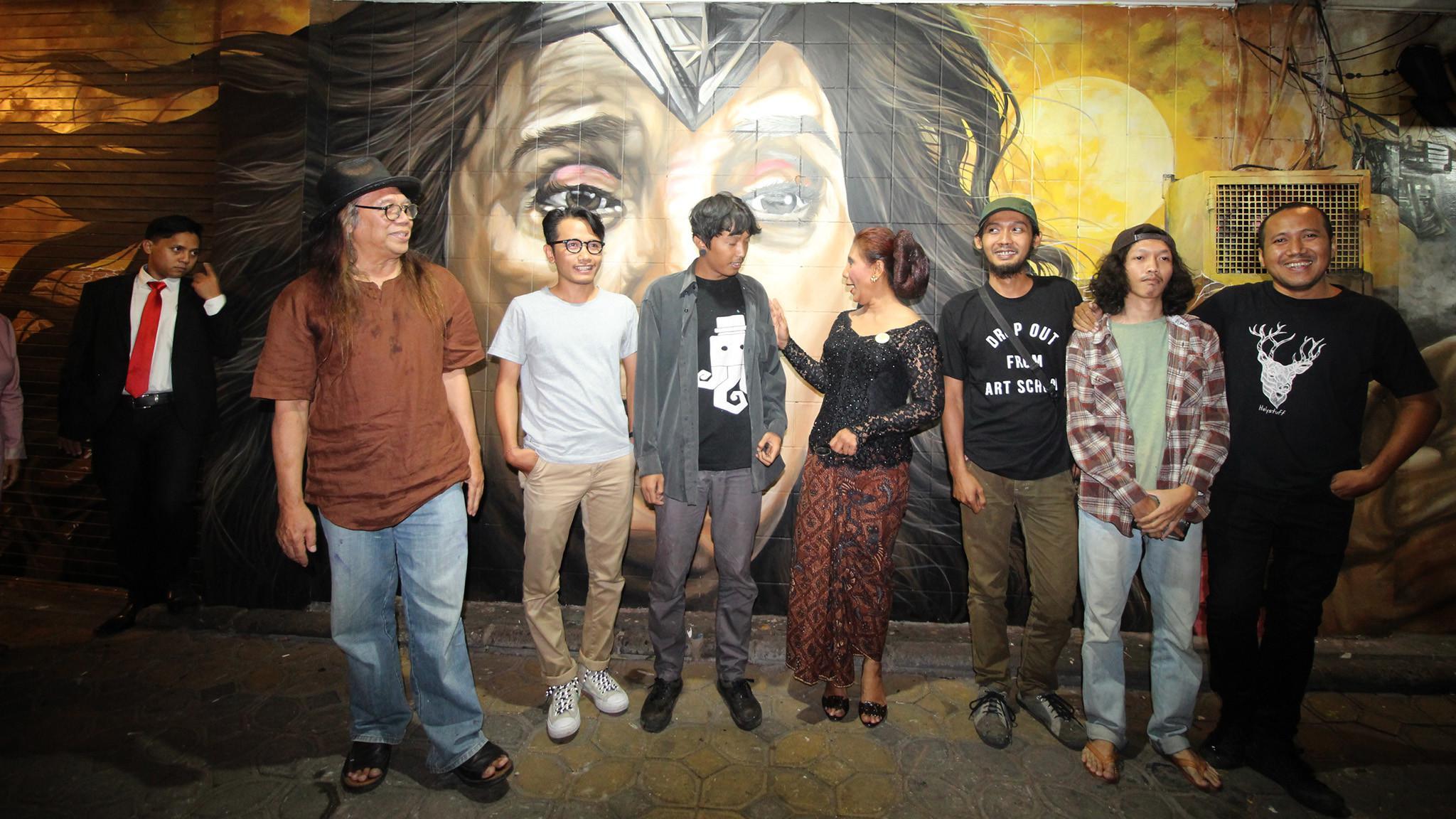 Menteri Susi Pudjiastuti bersama dengan para pelukis yang menggambar Susi Pudjiastuti bak Wonder Woman berpose di depan lukisan