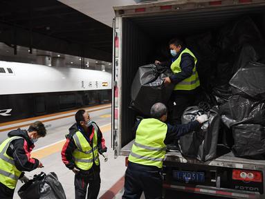 Para pekerja menurunkan paket dari sebuah truk di Stasiun Kereta Barat Beijing di Beijing, ibu kota China (1/11/2020). Otoritas perkeretaapian China meluncurkan layanan khusus pada Minggu (1/11), yang akan berlangsung hingga 20 November. (Xinhua/Zhang Chenlin)
