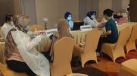 Pemberian vaksin Covid-19 kepada masyarakat di salah satu hotel di Pekanbaru.  (Liputan6.com/M Syukur)