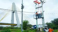 Petugas PLN Riau tengah memasang instalasi listrik. (Liputan6.com/Dok PLN Riau/M Syukur)
