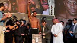 Petinju kelas berat Anthony Joshua (tengah) mengangkat tangannya saat timbang badan resmi di Riyadh, Arab Saudi, Jumat (6/12/2019). Anthony Joshua menantang Andy Ruiz Jr untuk merebut kembali sabuk juara kelas berat WBA, WBO, dan IBF. (AP Photo/Hassan Ammar)