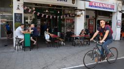 Pengunjung makan di luar di sebuah restoran di Tel Aviv, Israel pada Rabu (27/5/2020). Setelah lebih dari dua bulan ditutup untuk membendung penularan virus corona, restoran hingga kafe di Israel diizinkan dibuka kembali hari Rabu, 27 Mei. (AP Photo/Sebastian Scheiner)