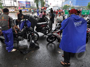 Sejumlah pengendara Motor mencoba menyalakan kendaraannya yang mati akibat menerjang banjir di Jalan Gunung Sahari, Jakarta, Senin (6/2/2015).  (Liputan6.com/Faizal Fanani)