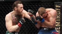 Conor McGregor (kiri) bertarung melawan Donald 'Cowboy' Cerrone pada pertarungan kelas welter UFC 246 di T-Mobile Arena, Las Vegas, Amerika Sertikat, Sabtu (18/1/2020). McGregor mengalahkan Cowboy pada detik ke-40. (AP photo/John Locher)