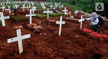 Seorang wanita melayat di TPU Pondok Ranggon, Jakarta, Selasa (8/12/2020). TPU Pondok Ranggon untuk saat ini hanya menerima pemakaman  korban covid-19 untuk Nasrani. (merdeka.com/Arie Basuki)