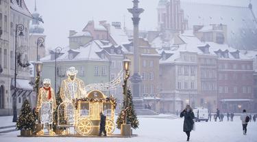 Sejumlah warga berjalan di Kota Tua saat hujan salju pertama mengguyur Warsawa, Polandia, pada 10 Desember 2020. Warsawa menyambut salju pertamanya tahun ini pada Kamis (10/12). (Xinhua/Jaap Arriens)