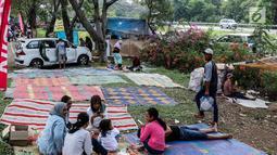 Sejumlah pemudik beristirahat sejenak di halaman rest area Tol Timur - Palimanan - Kanci,  Cirebon, Jawa Barat, Sabtu (1/7). Pada H+6 Lebaran pengguna jalan tol memanfaatkan rest area untuk makan, tidur sejenak. (Liputan6.com/Faizal Fanani)