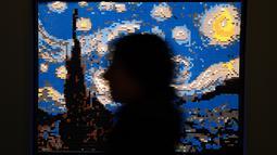 "Seseorang berdiri di dekat patung ""Starry night"" yang terbuat dari susunan balok lego pada pameran Art of the Brick di Turin, Italia, Kamis (15/11). Pameran tersebut menampilkan berbagai patung lego karya seniman AS, Nathan Sawaya. (MARCO BERTORELLO/AFP)"