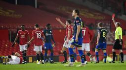 Wasit memberikan kartu merah kepada pemain Southampton, Alex Jankewitz, saat melawan Manchester United pada laga Liga Inggris di Stadion Old Trafford, Selasa (2/2/2021). Setan Merah menang dengan skor 9-0. (Laurence Griffiths/Pool via AP)