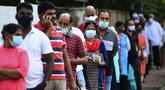 Para pemilih mengenakan masker saat antre di luar tempat pemungutan suara di Kolombo, Sri Lanka, Rabu (5/8/2020). Sri Lanka menggelar pemilihan parlemen di tengah pandemi COVID-19. (Ishara S. KODIKARA/AFP)