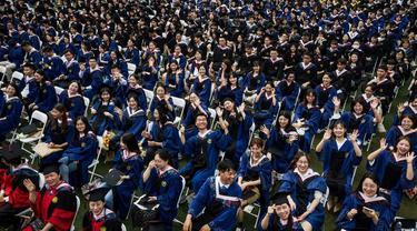 Para siswa di Wuhan muncul secara massal dengan jubah dan papan mortir untuk upacara kelulusan di Central China Normal University dan tentunya tanpa masker (AFP)
