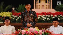 Presiden Joko Widodo atau Jokowi (tengah) didampingi Wapres Jusuf Kalla (kanan) dan Ketua MPR Zulkifli Hasan memberi sambutan saat menerima pimpinan lembaga negara untuk buka puasa bersama di Istana Negara, Jakarta, Senin (6/5/2019). (Liputan6.com/Angga Yuniar)