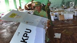 Petugas Linmas menyelamatkan kotak suara kardus yang sebagian rusak terendam banjir di gudang tempat penyimpanan logistik di Kecamatan Ciseeng, Bogor, Senin (15/4). Lebih dari 600 kotak suara rusak akibat tembok gudang jebol diterpa hujan lebat dan angin kencang semalam. (merdeka.com/Arie Basuki)