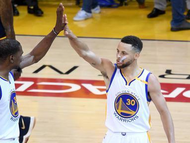 Pemain Golden State Warriors Kevin Durant (35) dan Stephen Curry (30) melakukan selebrasi saat bertanding melawan Cleveland Cavaliers di gim pertama Final NBA 2017 di Oracle Arena di Oakland, California (1/6). (Thearon W. Henderson/Getty Images/AFP)