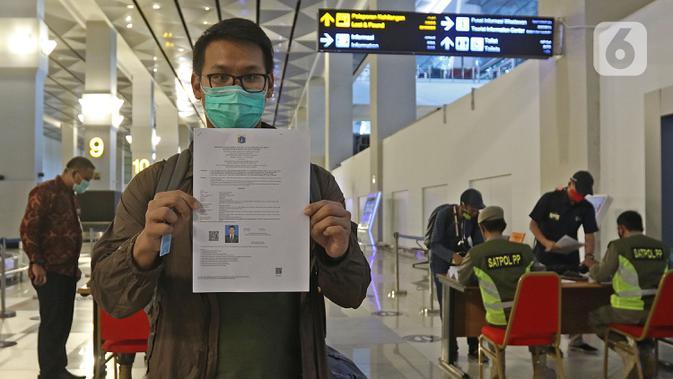Penumpang menunjukkan SIKM di terminal 3 kedatangan domestik bandara Soekarno Hatta, Tangerang, Banten, Rabu (27/5/2020). Bandara Soetta memberlakukan Tiga checkpoint di terminal kedatangan salah satunya pemeriksaan SIKM dan doukumen kesehatan setiap penumpang. (Liputan6.com/Herman Zakharia)