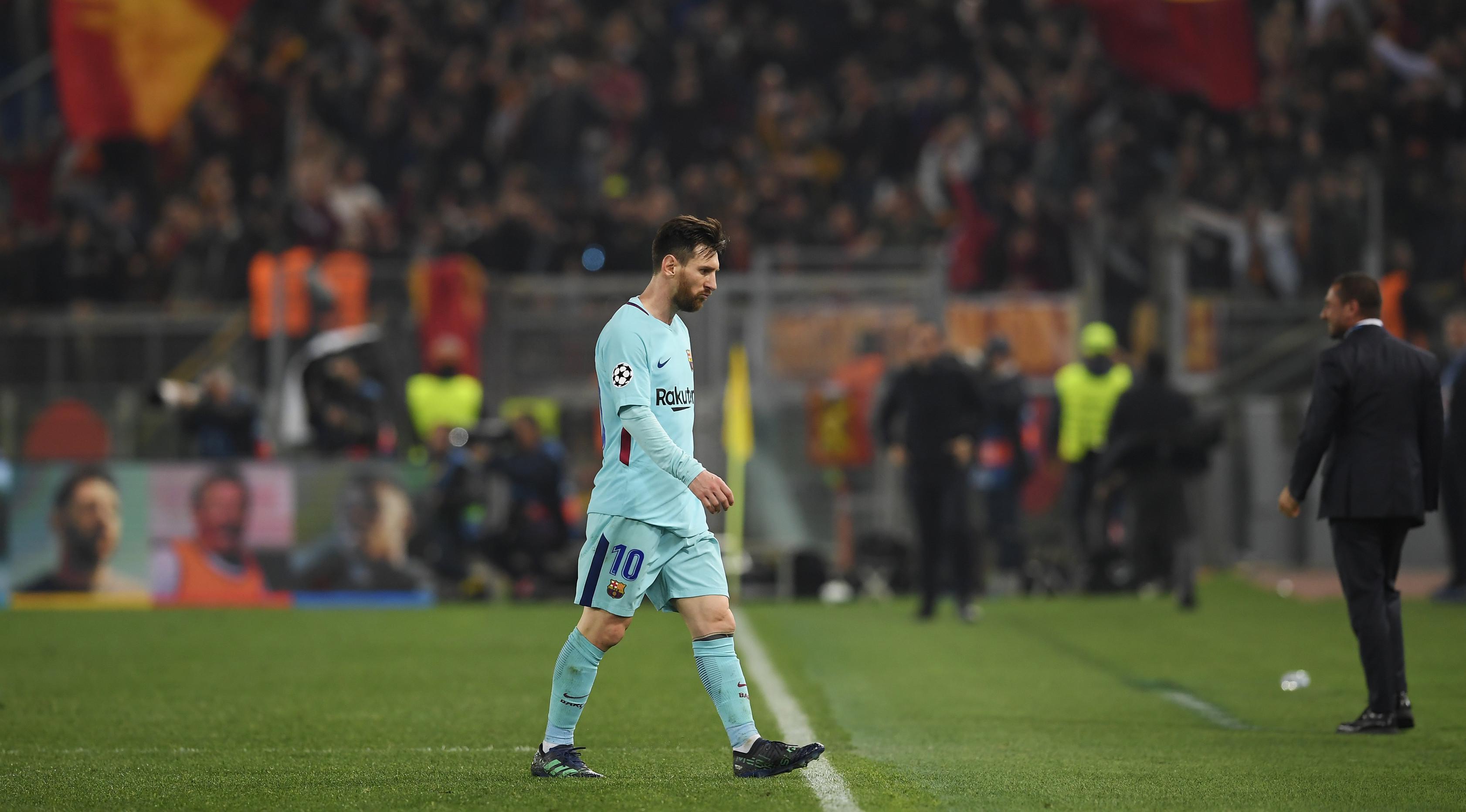 Pemain Barcelona, Lionel Messi tertunduk meninggalkan lapangan usai kalah dari AS Roma pada laga leg kedua perempat final Liga Champions di Stadion Olimpico, Selasa (10/4). Bercelona tersingkir setelah menyerah 0-3 dari AS Roma. (Andreas SOLARO/AFP)