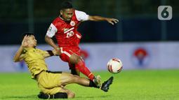 Pemain Bhayangkara Solo FC TM Ichsan (kiri) berebut bola dengan gelandang Persija Jakarta Ramdani Lestaluhu pada laga Piala Menpora 2021 di Stadion Kanjuruhan, Malang, Rabu (31/3/2021). Persija menang 2-1. (Bola.com/M Iqbal Ichsan)