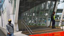 Petugas berjaga di depan pintu masuk menuju stasiun MRT Benhil, Jakarta, Selasa (29/4/2020). PT MRT Jakarta (Perseroda) menutup sementara layanan Stasiun Bendungan Hilir (Benhil) dan Stasiun Senayan sebagai bentuk dukungan penerapan pembatasan sosial berskala besar (PSBB). (Liputan6.com/Johan Tallo)