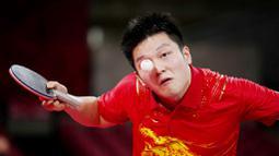 Petenis China, Fan Zhendong, saat bertanding melawan atlet tenis meja Portugal, Marcos Freitas, pada babak 16 besar Olimpiade Tokyo 2020, Selasa, (27/7/2021). (Foto: AP/Kin Cheung)