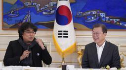 Sutradara Bong Joon Ho berbicara di sebelah Presiden Korea Selatan Moon Jae-in saat makan siang di Blue House, Seoul, Kamis (20/2/2020). Presiden Moon mengundang Sutradara Bong Joon Ho dan seluruh tim untuk merayakan kemenangan Parasite yang membawa pulang empat Piala Oscar 2020. (KIM HONG-JI/AFP)