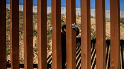 Kevin Andres, seorang anak imigran Meksiko berusaha memanjat pagar perbatasan AS (28/12). Banyak Imigran dari karavan memilih menyeberangi tembok perbatasan AS dan menyerahkan diri kepada agen patroli perbatasan. (AP Photo/Daniel Ochoa de Olza)