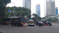 Sejumlah personel Kepolisian dan Satuan Polisi Pamong Praja (Satpol PP) telah bersiaga di kawasan Bundaran Hotel Indonesia (HI), Menteng, Jakarta Pusat untuk mengamankan aksi buruh. (Liputan6.com/Ika Defianti)