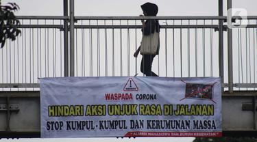 Pejalan kaki melintasi Jembatan Penyeberangan Orang (JPO) di Jalan Raya Lenteng Agung, Jakarta, Selasa (17/3/2020). Sebuah spanduk berisi ajakan menghindari kerumunan dan kumpul-kumpul untuk mencegah penyebaran virus Corona COVID-19 terpasang di JPO teresebut. (Liputan6.com/Helmi Fithriansyah)
