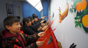 Para siswa belajar memainkan wayang kulit di Sekolah Dasar Xiyoucun di Kota Shahe, Provinsi Hebei, China utara, pada 24 November 2020. (Xinhua/Fan Shihui)