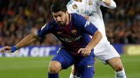 Pemain Barcelona, Luis Suarez dan pemain Real Madrid, Cristiano Ronaldo berebut bola pada pertandingan La Liga Spanyol di Stadion Camp Nou, Minggu (6/5). Real Madrid yang bermain dengan 11 pemain gagal mengalahkan 10 pemain Barcelona (AP/Emilio Morenatti)