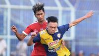 Vikrian Akbar (Biru) beduel dengan seniornya, Jayus Hariono dalam uji coba Arema FC versus Arema U-21 pada Minggu (16/6/2019) di Stadion Kanjuruhan, Kab. Malang. (Bola.com/Iwan Setiawan)