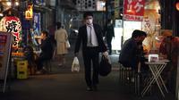 Seorang pria yang mengenakan masker berjalan mlewati bar jalanan di Tokyo, Jepang, 28 April 2020. Pandemi virus corona COVID-19 mengadu kelompok yang bersedia mengikuti peraturan tetap tinggal di rumah dengan mereka yang menolaknya. (AP Photo/Eugene Hoshiko, File)