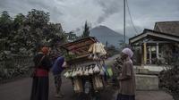 Gunung Semeru menjulang sehari setelah erupsi di atas desa Lumajang, Jawa Timur, pada Minggu (17/1/2021). Kendati demikian, Pusat Vulkanologi dan Mitigasi Bencana Geologi ( PVMBG) menegaskan status Semeru masih level II atau Waspada. (Juni Kriswanto / AFP)