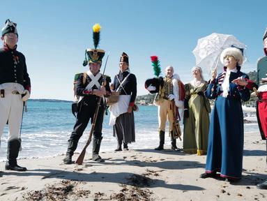 Orang-orang yang mengenakan kostum era Napoleon Bonaparte berdiri di pantai dalam rangka peringatan 200 tahun kematian Napoleon Bonaparte, Saint-Helene, Golfe-Juan, Prancis, 16 Maret 2021. Napoleon adalah pemimpin militer dan politik Prancis yang terkenal saat Perang Revolusioner. (Valery HACHE/AFP)