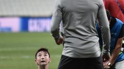Seorang anak tanpa memiliki kaki menyundul bola saat bermain dengan gelandang Liverpool, Mohamed Salah saat sesi pelatihan jelang bertanding melawan Chelsea pada Piala Super Eropa 2019 di Stadion Taman Besiktas, di Istanbul (13/8/2019). (AFP Photo/Ozan Kose)