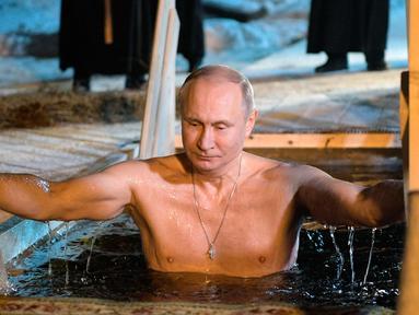 Presiden Rusia Vladimir Putin berendam di air dingin di Danau Seliger di desa Svetlitsa, Rusia (19/1). Ribuan pengikut Gereja Ortodoks Rusia akan berendam ke sungai dan kolam es merayakan Epiphany. (Alexei Druzhinin, Sputnik, Kremlin Pool Photo via AP)