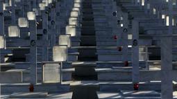 Kuburan dengan potrait tentara yang tewas dalam invasi Turki ke Siprus terlihat di pemakaman militer Tymvos Macedonitissas, Nicosia, Siprus, Senin (20/7/2020). Ribuan orang Yunani dan tentara Siprus tewas selama invasi Turki ke Pulau Siprus pada tahun 1974. (AP Photo/Petros Karadjias)