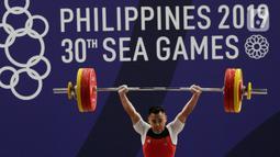 Lifter Eko Yuli melakukan angkatan saat SEA Games 2019 cabang angkat besi nomor 61 kg di Stadion Rizal Memorial, Manila, Filipina, Minggu (1/12/2019). Dirinya meraih emas dengan total angkatan 309 kg. (Bola.com/M Iqbal Ichsan)