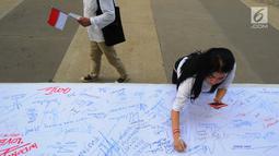Seorang wanita menandatangani kain putih saat melakukan deklarasi Indonesia Bangkit saat hari kebangktian nasional ke 111 tahun di GBK, Jakarta, Senin (20/5). Tujuan deklarasi ini untuk menyegarkan kembali ingatan dan tekad merawat persatuan Indonesia. (Liputan6.com/Angga Yuniar)