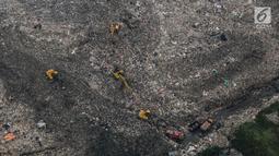 Pandangan udara terlihat alat berat mengeruk sampah di TPST Bantar Gebang, Bekasi, Jawa Barat, Selasa (4/6/2019). Kondisi TPST Bantar Gebang kian rapih, perapihan dilakukan dengan membuat bentuk seperti tangga dan semakin kecil pada bagian atasnya, mirip bentuk piramida. (Liputan6.com/Faizal Fanani)