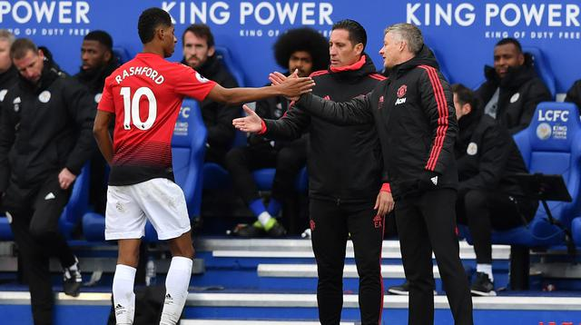 Striker MU, Marcus Rashford (kiri) berjabat tangan dengan manajer sementara MU Ole Gunnar Solskjaer (kanan) saat digantikan pada laga melawan Leicester City pada Premier League di King Power Stadium, Leicester, Minggu (3/2). (Ben STANSALL/AFP)