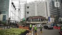 Pekerja memasang panggung untuk acara malam tahun baru di sekitar kawasan Bundaran HI, Jakarta, Rabu (25/12/2019). Merayakan pergantian tahun, Pemprov DKI Jakarta menggelar sejumlah acara di sejumlah titik sepanjang Jalan Sudirman-MH Thamrin. (Liputan6.com/Faizal Fanani)