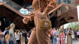 Luna Maya juga terlihat mengenakan blouse panthera chiffon bermotif panther warna coklat yang dipadukan dengan flare pants heather basket weave dengan warna senada dari Kate Spade. (Liputan6.com/IG/@lunamaya)