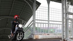 Pemotor melintasi jembatan penyeberangan orang (JPO) di kawasan Pasar Minggu, Jakarta, Rabu (24/4). Kurangnya kesadaran akan tertib berlalu lintas menyebabkan para pemotor itu nekat melintasi JPO, meskipun dapat merugikan hak pejalan kaki. (Liputan6.com/Immanuel Antonius)