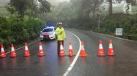 Polisi menutup jalan dan mengalihkan arus lalu lintas usai terjadi longsor di kawasan Puncak Bogor, Jawa Barat (6/2). Menurut pihak kepolisian setempat titik longsor saat ini bertambah dari empat menjadi enam lokasi. (Liputan6.com/Pool/Polres Bogor)