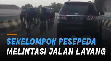 Sekelompok pesepeda terekam melintas  jalan layang yang di situ terdapat rambu larangan sepeda tidak boleh melintas.