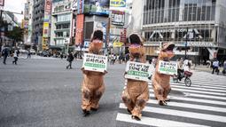 Aktivis kelompok hak hewan PETA mendesak orang untuk menjadi vegan selama protes di Tokyo, Jepang, Rabu (6/10/2021). Dalam aksinya, para aktivis mengenakan kostum dinosaurus. (CHARLY TRIBALLEAU/AFP)